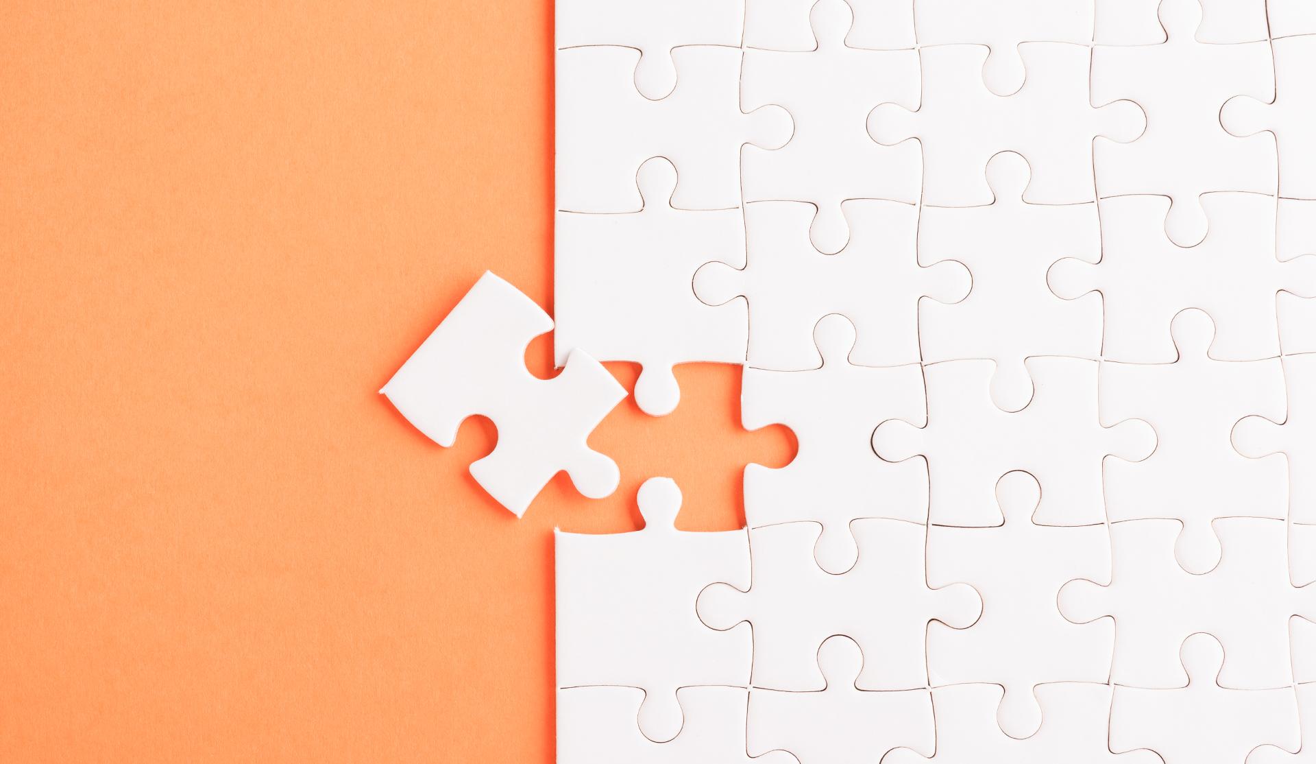pieza puzzle blanca sobre fondo naranja
