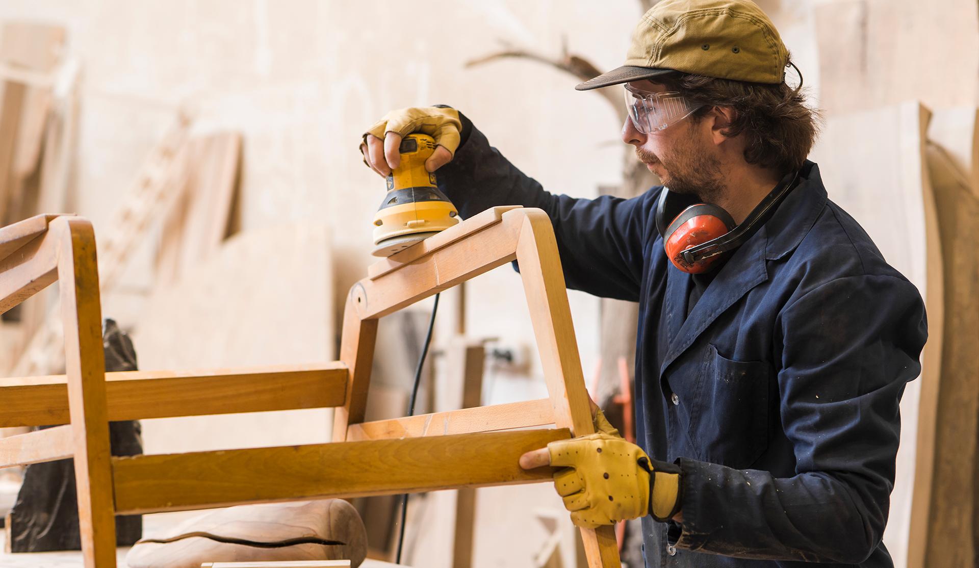 hombre carpintero lijando madera