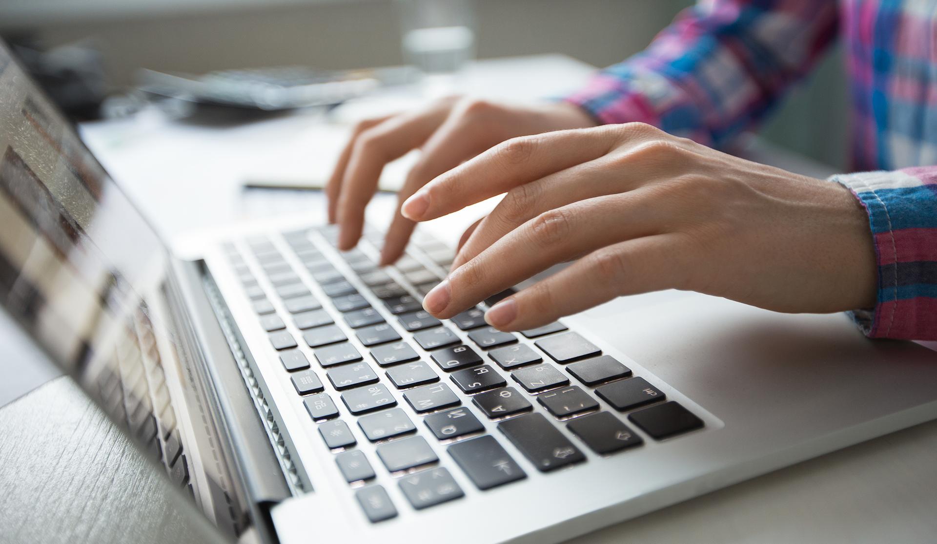 primer plano manos de mujer escribiendo en teclado