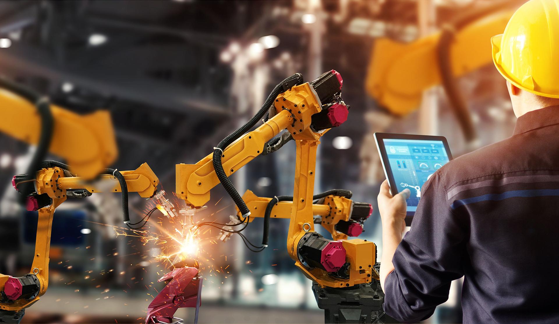 Operario con tablet controlando brazo robótico en producción