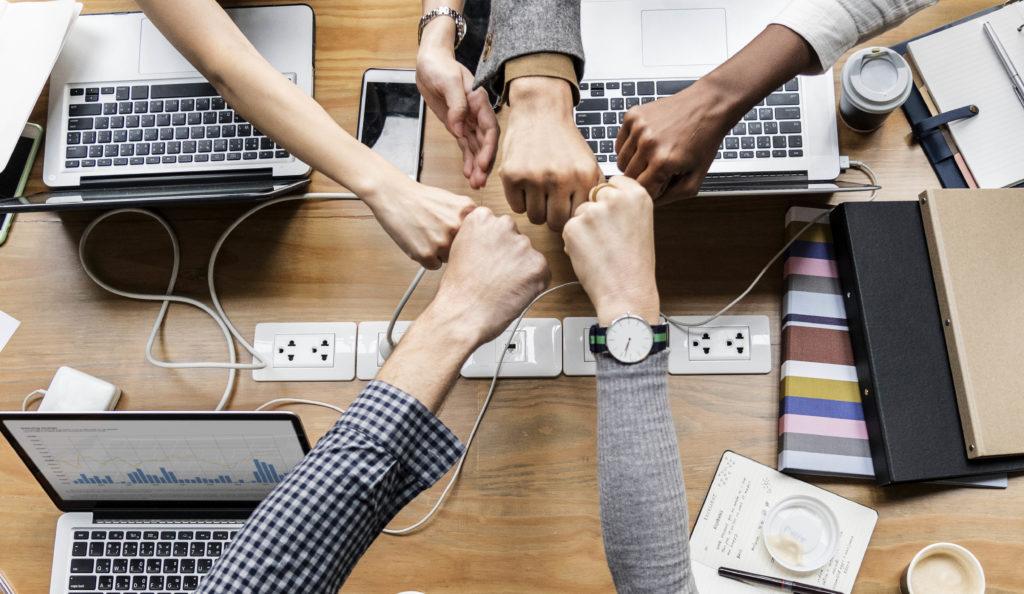 equipo de trabajo juntando manos vista superior